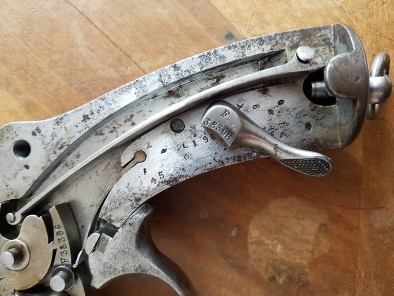 démontage revolver modèle 1873: Pousser vers le bas la clé de débrayage du grand ressort