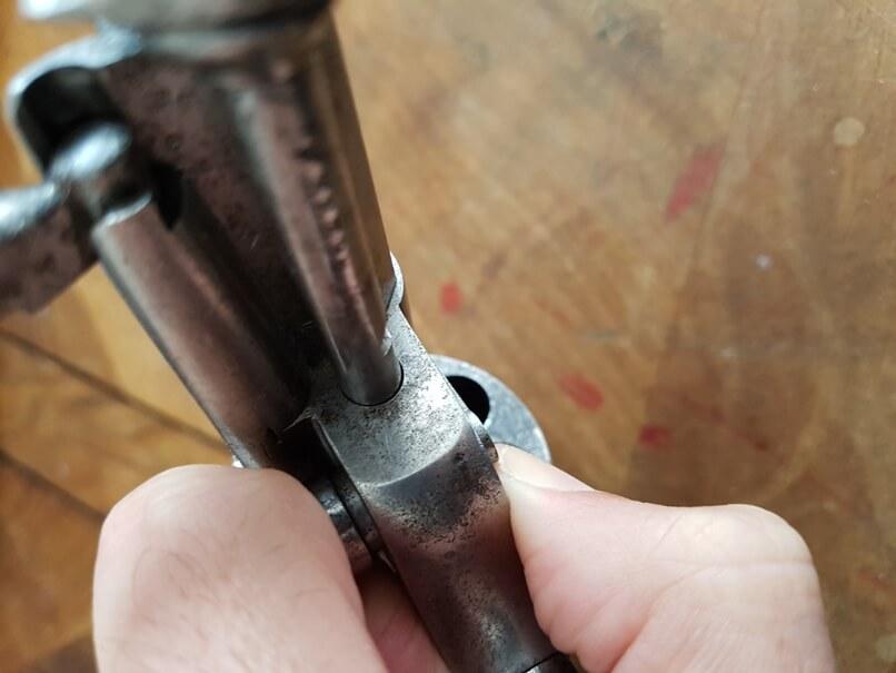 démontage revolver modèle 1873: Appuyer sur le bouton poussoir de l'axe de barillet, et tirer l'axe de barillet vers l'avant