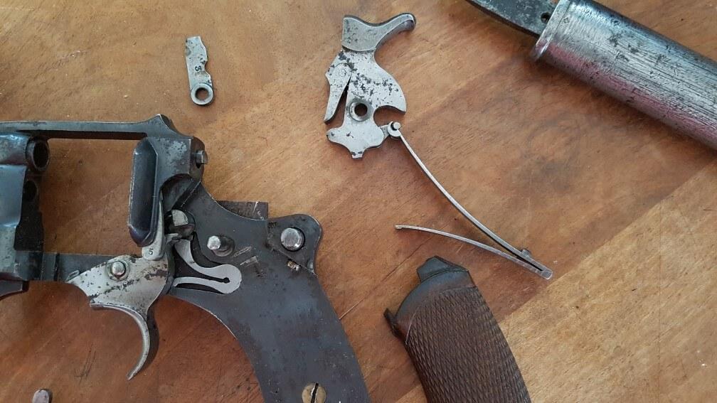 démontage Revolver modèle 1887: Oter le chien et grand ressort, en les tirants simultanément, vers le haut. Bien dégager le tenon du grand ressort de son encastrement